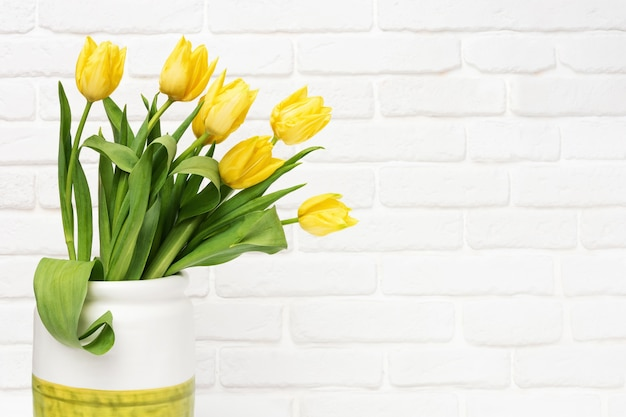 Spring flowers of tulip in vase on decorative brick wall