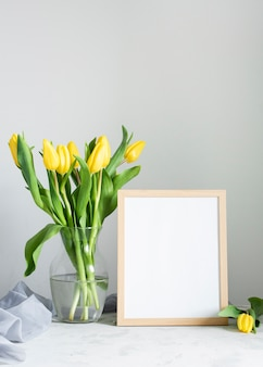 Spring flowers in vase with frame beside