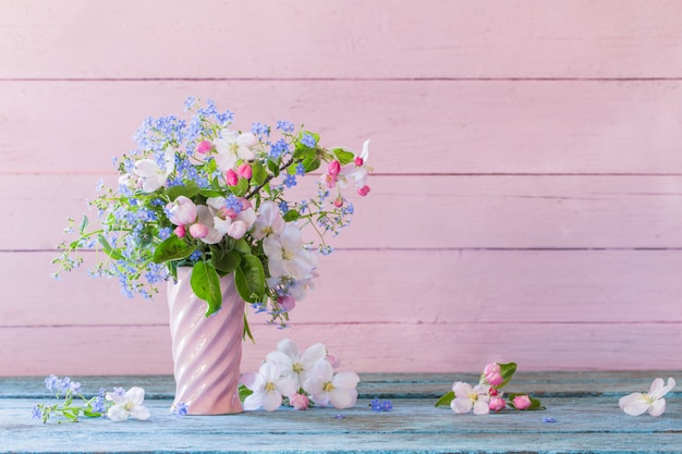 Spring flowers in vase on wooden wall