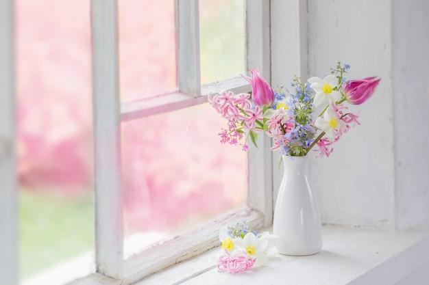 Spring flowers in white vase on old windowsill