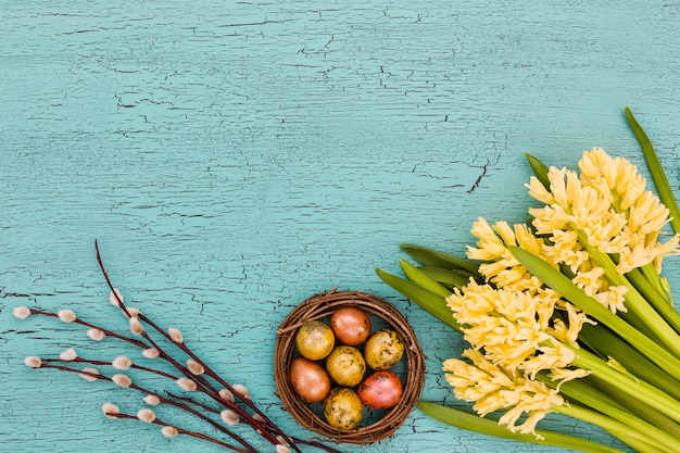 Spring flowers, willow branch and easter eggs on blue wall. copy space, top
