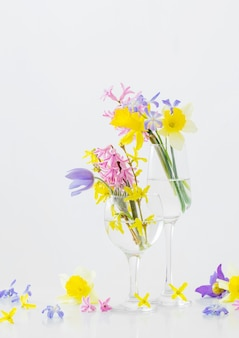 Spring flowers in wineglass on white surface