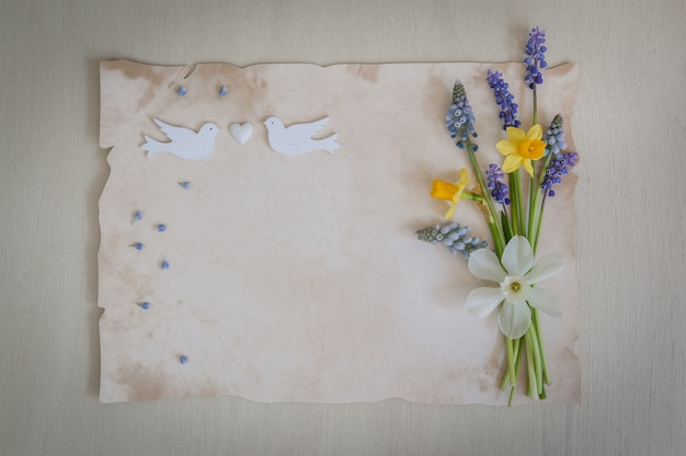 Spring flowers with paper for text and two wooden birds and heart. wedding, engagement or betrothal concept on on a wooden background.copy space, top view. greeting card. .