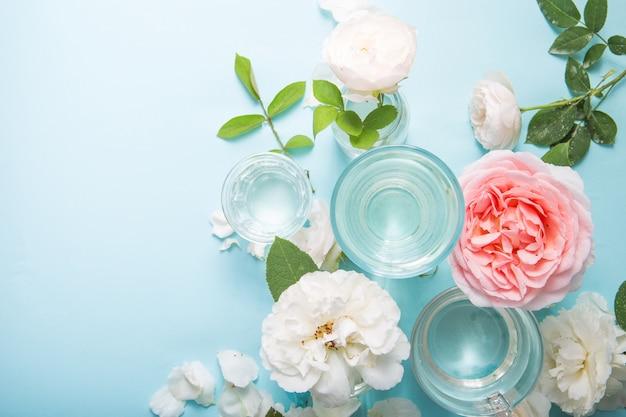 青のガラスの液体の水を通して歪んだ春の新鮮な白、ピンクのバラ