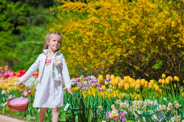 Spring garden, spring flowers, adorable little girl and tulips. cute kid with a basket in blooming garden on warm day