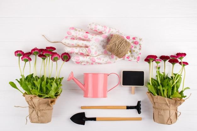春の庭の作品コンセプト。園芸工具、鉢花、水まき缶白いテーブルの上。トップビュー、フラットレイアウト Premium写真