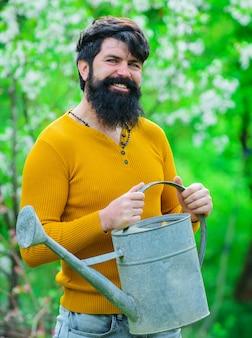 春のガーデニング、じょうろを持つひげを生やした庭師。植栽の準備をしている笑顔の男。
