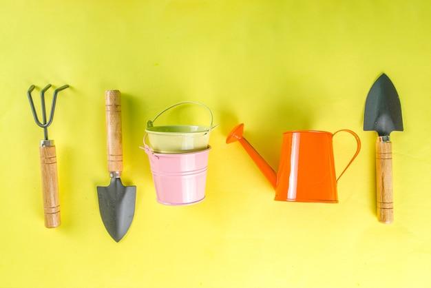 봄 원예 개념. 원예 도구, 허브 및 식물, 노란색 벽에 flatlay. 봄 야외 정원 작동 개념.