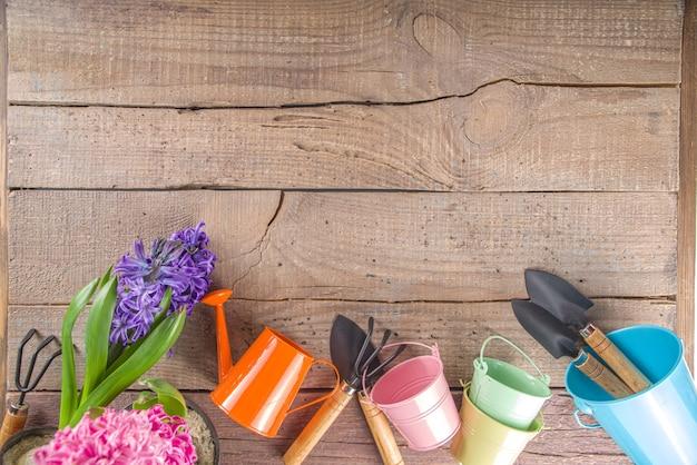 봄 원예 개념. 원예 도구, 허브 및 식물 소박한 야외 나무 테이블에. 봄 야외 정원 작동 개념.