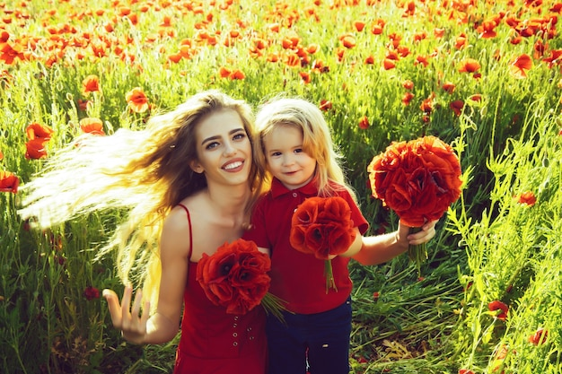 Spring girl and little boy or child in field of poppy.