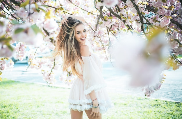 Spring girl in short pink dress enjoying sunny day in garden female playing with long gorgeous blond hair beauty and hair care products sexy woman posing under blooming cherry blossom tree