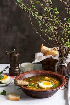 ハーブ、野菜、エンドウ豆の春のグリーンスープ。卵とサワークリームを添えて。素朴なスタイル。