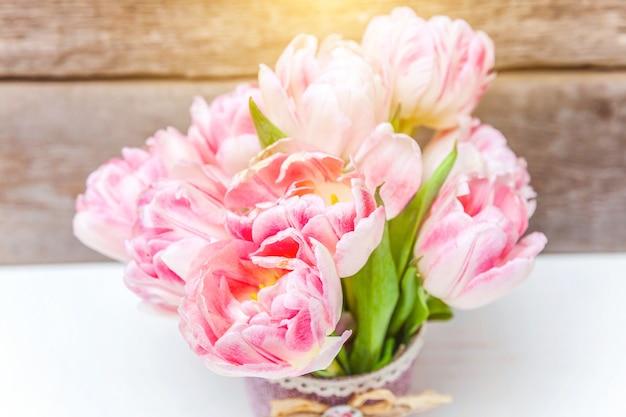 봄 인사말 카드. 나무 배경에 신선한 빛 파스텔 핑크 튤립 꽃의 꽃다발