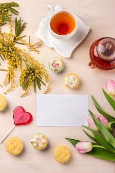 Spring greeting card with tulips, mimosa, tea and cupcakes on wooden background.