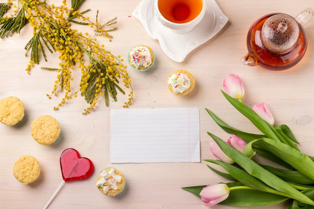 Spring greeting card with tulips, mimosa, tea and cupcakes on wooden table.