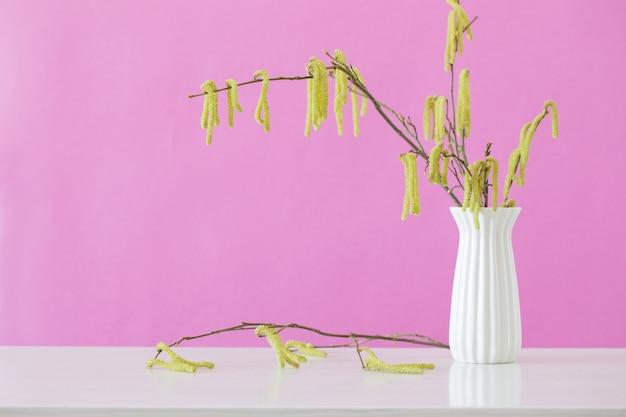 Spring hazel branches in white vase on pink background