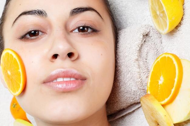 봄, 건강, 사람, 젊음, 아름다움 개념 - 천연 수제 과일 얼굴 마스크. 신선한 과일입니다. 페이셜 클렌징 마스크를 적용하는 스파 여자. 뷰티 트리트먼트