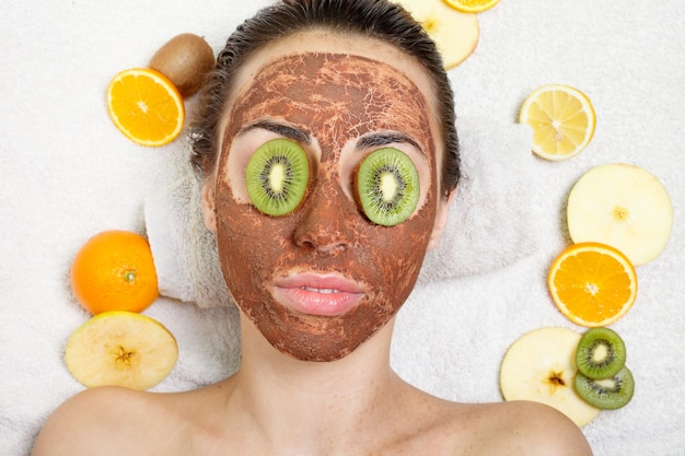 Spring, health, people, youth and beauty concept -natural homemade fruit facial masks. fresh fruit. spa woman applying facial cleansing mask. beauty treatments