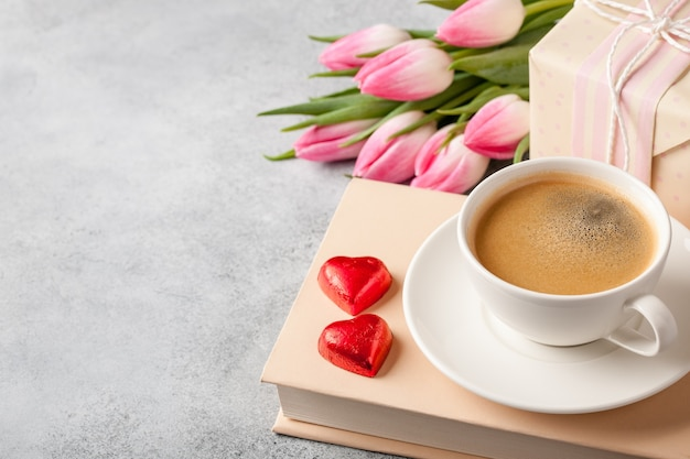 Spring holiday concept. coffee, book, tulips and gift box.