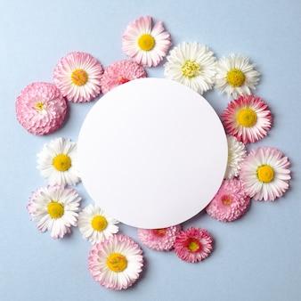 春の休日のコンセプトです。色とりどりの花とパステルブルーの背景の空白の円形の紙カードで作られた創造的なレイアウト。