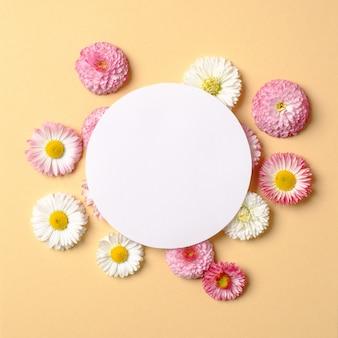 春の休日のコンセプトです。色とりどりの花とパステルイエローの背景の空白の円形の紙カードで作られた創造的なレイアウト