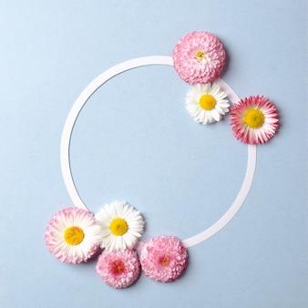 春の休日のコンセプトです。色とりどりの花とパステルブルーの背景の空白の円形の紙カードのアウトラインで作られた創造的なレイアウト。