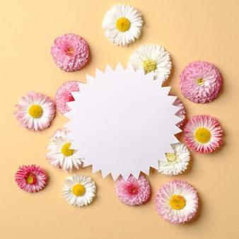 春の休日のコンセプトです。色とりどりの花で作られた創造的なレイアウトとパステルイエローの背景の空白の歯車形の紙カード。
