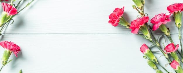 春休みは、明るいターコイズ色の木の表面にピンクのカーネーションの花束が平らに横たわっていました。コピースペースのある上面図。バナー