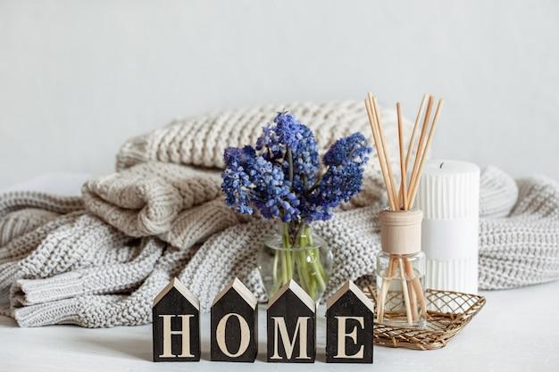 Весенняя домашняя композиция с цветами, ароматическими палочками, вязанным элементом и декоративным словом home.