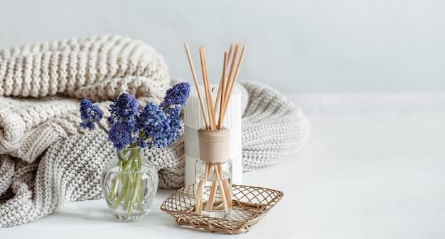Composizione casa primaverile con fiori, bastoncini aromatici e spazio copia elemento a maglia.