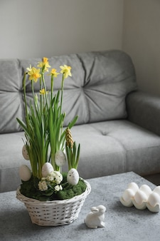 Spring home interior with easter tree and vase with painted eggs