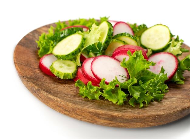 Весенний домашний салат из редиса со свежим огурцом и зеленью на деревянной изолированной тарелке. простой зеленый деревенский салат с нарезанным редисом, огурцами, эскаролом и листьями салата