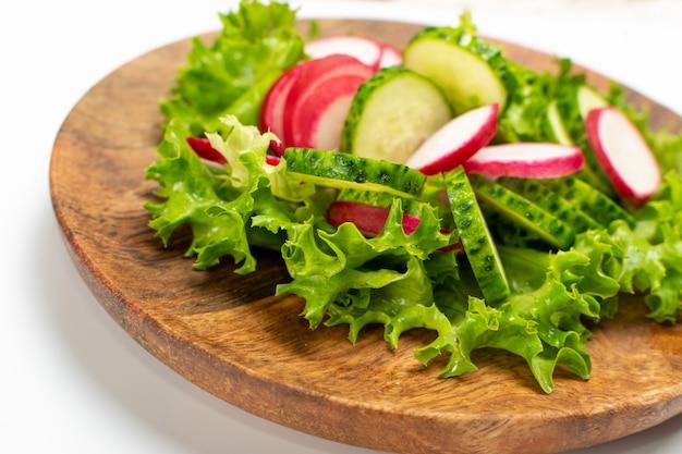 Весенний домашний салат из редиса со свежим огурцом и зеленью на деревянной тарелке. простой зеленый деревенский салат с нарезанным редисом, огурцами, эскаролом и листьями салата