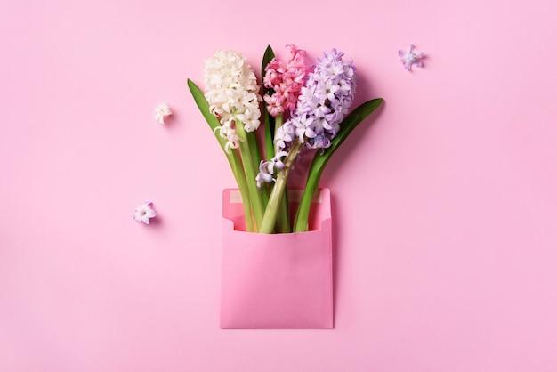 Spring hyacinth flowers in pink postal envelope over punchy pastel background.