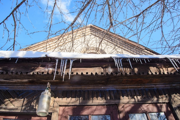 Spring icicles hanging from the roof of the old house