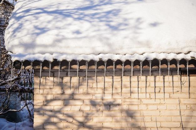 Весенние сосульки свисают с крыши старых кирпичных домов с заснеженной крышей