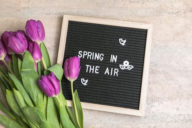 レターボードと紫色のチューリップの花の花束の空中春