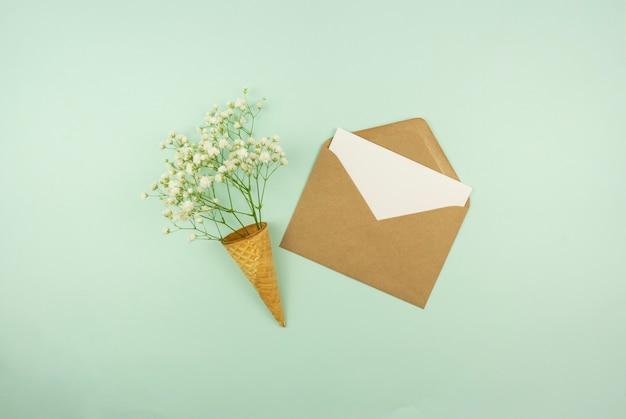 Весна идет концепция. заготовка в коричневом конверте со свежими цветами в вафельном рожке.