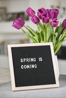 レターボードと紫のチューリップの花の花束に春が来ています