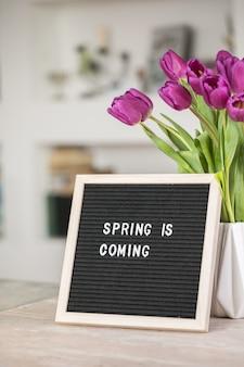 レターボードと紫のチューリップの花の花束に春が来ています Premium写真