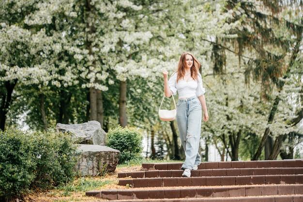 春がやってきました。長い睡眠の後の自然の復活。日本の咲くエメラルドガーデンの優しい女性の肖像画。屋外で珍しいライフスタイル活動で幸せなかわいい女の子を笑顔の女性らしさ