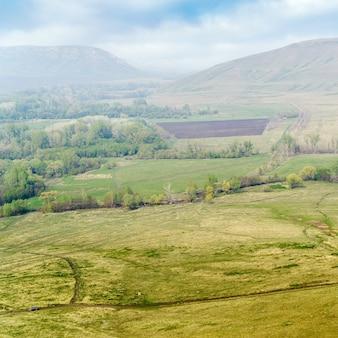 러시아 andreevka 마을 근처 산골짜기의 경작된 들판이 있는 봄 풍경