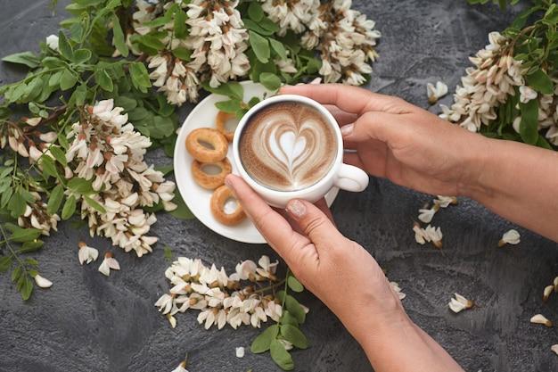 女性の手にコーヒーと白いアカシアの花と春のレイアウト。