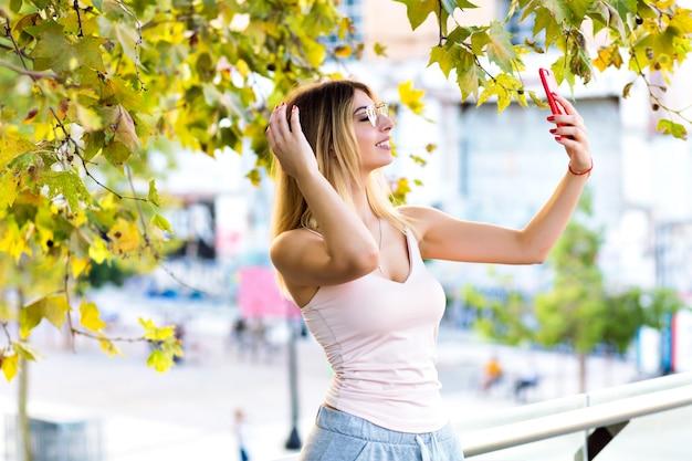 Ritratto di stile di vita primaverile di donna abbastanza bionda che fa selfie e parla in chat video con la sua amica, vestiti sportivi casual, colori pastello soleggiati.
