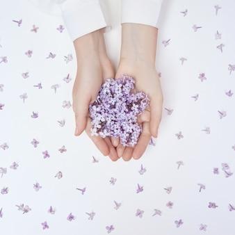 白いテーブルに横たわっている女性の手に春のユリの花。手のための自然な化粧品、しわ防止の手。女性の自然の美しさ