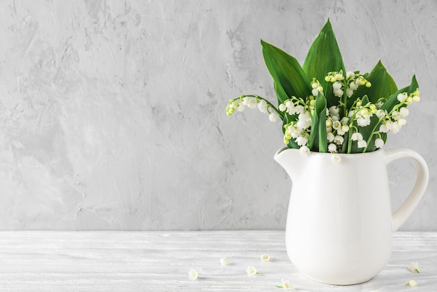 Spring lily of the valley flowers in vase on concrete background with copy space. still life
