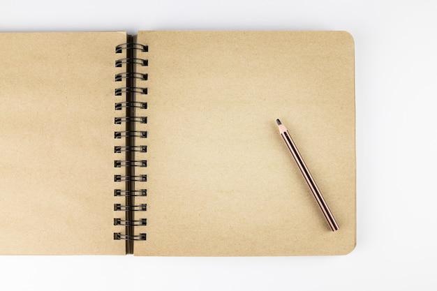 스프링이 장착된 노란색 종이는 흰색 표면에 노트북과 연필을 열었습니다.