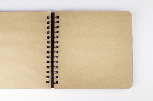 흰색 표면에 스프링이 장착된 노란색 종이 열린 노트북, 평평한 평지