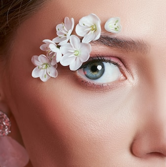 Spring makeup eye woman with white flowers. creative floral beauty eye makeup. eyelashes cosmetic summer flowers