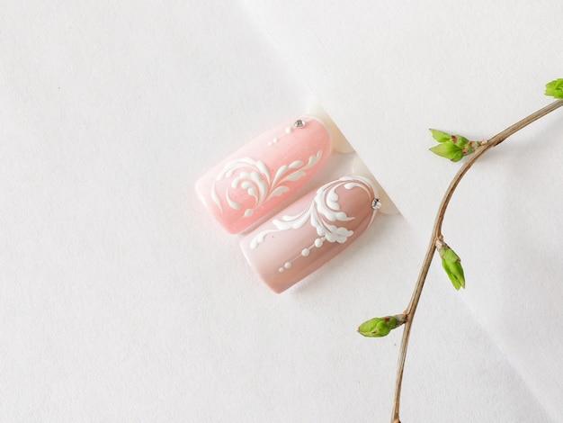 春のマニキュア。白いテーブルにピンクのモノグラムデザインのヒント。
